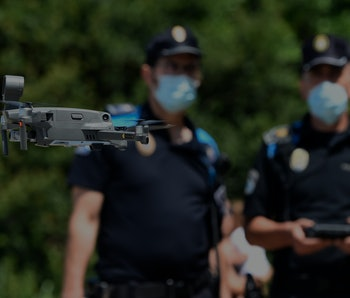 Two masked police officers operate a small drone.