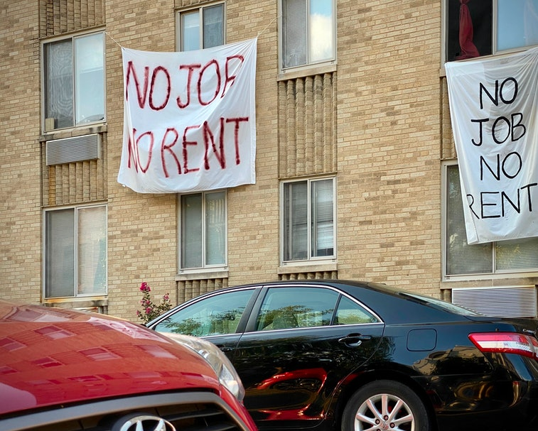A sign hangs from an apartment window. The letters are written in red paint. It reads: No job, no rent.