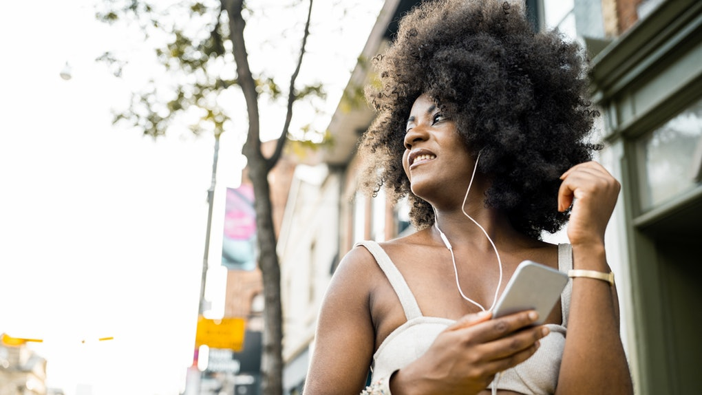A young Black woman walks around in a city during the summer with her headphones in.