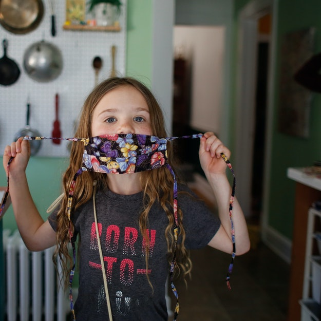 little girl putting on her face mask
