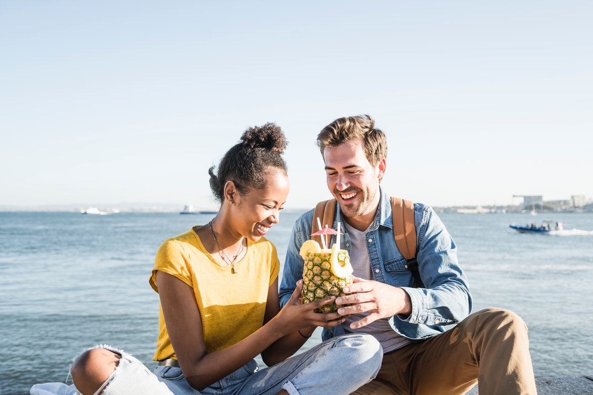 A young couple sits nears the beach, and enjoys a drink in a pineapple with straws and a tiny umbrella.