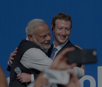 The prime minister of India, Narendra Modi, can be seen hugging Facebook CEO Mark Zuckerberg. Modi has traditional Indian clothes on in the form of a Nehru jacket and white kameez. Zuckerberg is wearing a suit. The background is blue.