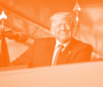 The United States president Donald Trump can be seen mid-smile during a rally. He is wearing a red tie, a blue blazer. He is standing behind a podium.