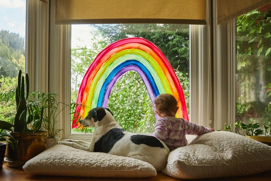baby and dog in front of window with rainbow painted on it