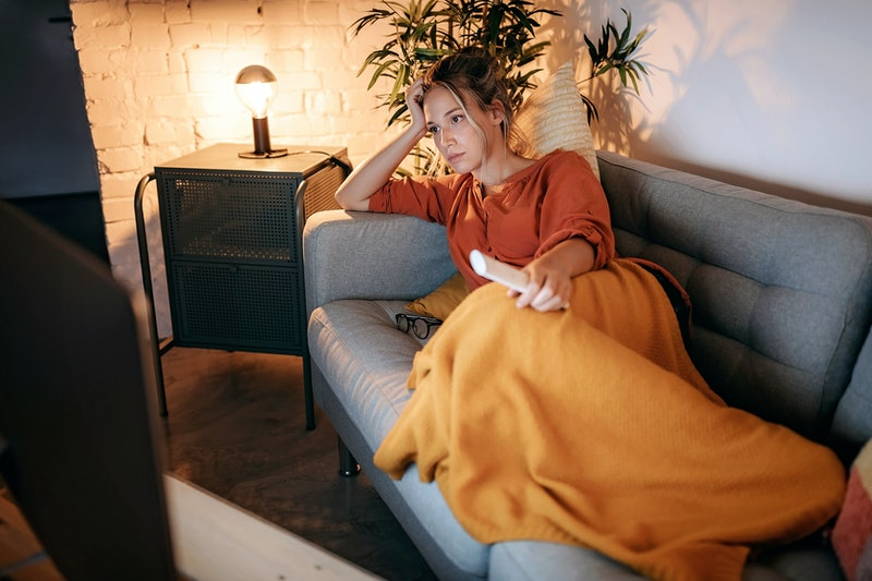 A woman is annoyed while lying on her couch with a yellow blanket. Experts explain why the covid-19 pandemic is making people irritable.
