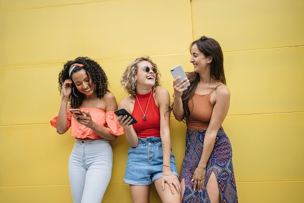 Three best friends laugh at something on their phones, while standing next to a yellow wall.