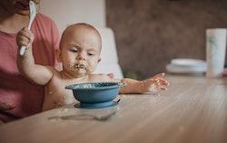 baby eating mashed avocado
