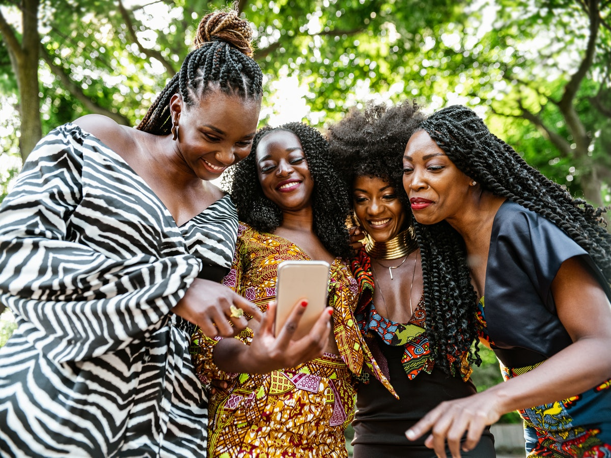 A group of friends huddle around to see something funny on a phone.