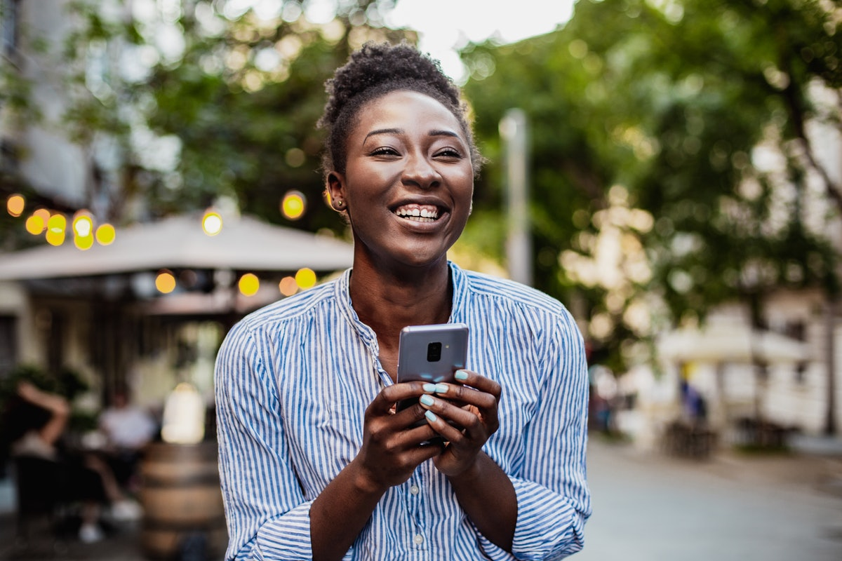 A happy woman laughs at something on her phone.