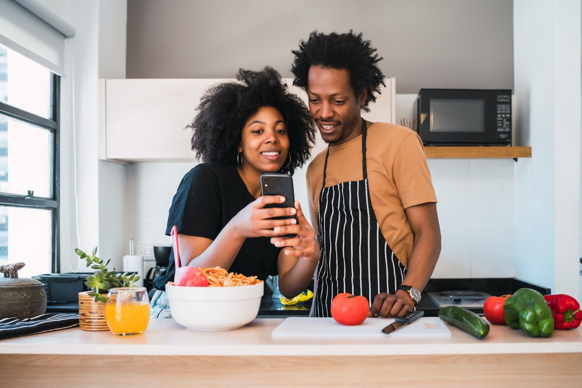A couple looks at their phone in the kitchen, while cooking together.