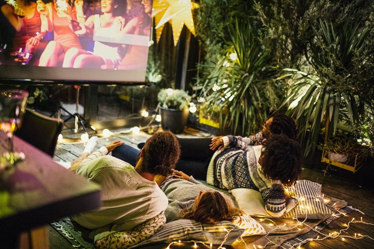 Two young couples lay on a palette with a blanket and lights on it, and watch a movie outdoors on a projector screen.