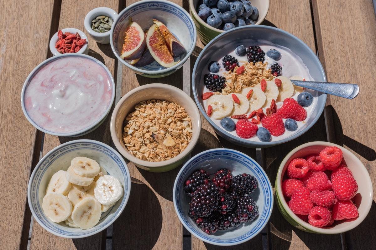 A smoothie bowl sits on a picnic table along with ingredients like fresh fruit, seeds, and granola to go into it.