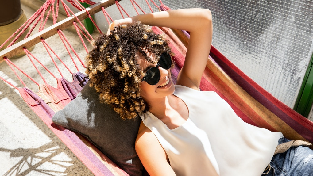 A young Black woman lays on a colorful hammock on her balcony, while wearing a pear of sunglasses and white tank top.