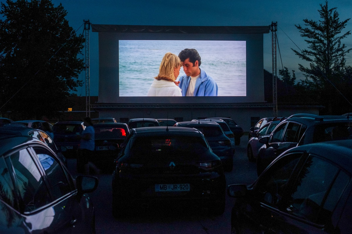 A bunch of cars line up at a drive-in theater to watch 'Grease.'