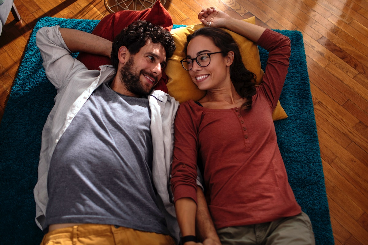 A happy couple camps out in their living room on the floor.