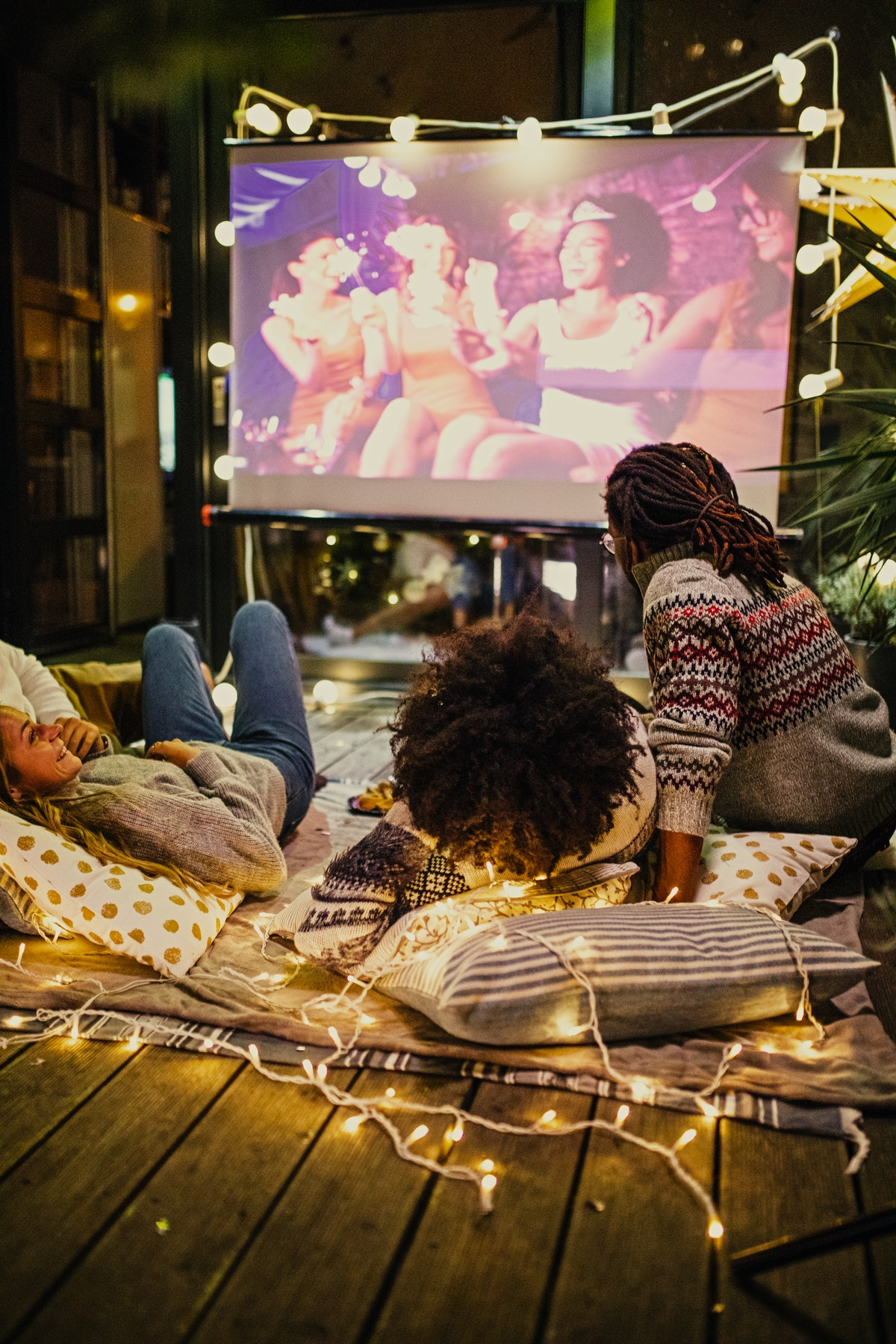 Two couples sit on a blanket that's lined with lights and watch a movie on a projected screen.