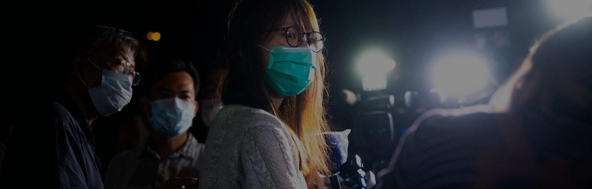Activist Agnes Chow is lit by harsh lights as she's interviewed in Hong Kong.