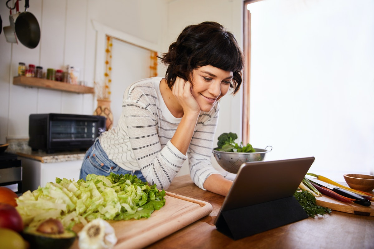 A young woman looks at her tablet while standing in her kitchen with chopped-up produce on a cutting board.