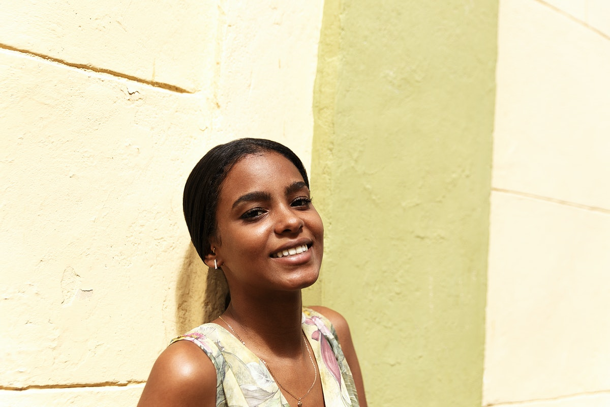 A young woman poses against a light yellow wall on a sunny day.