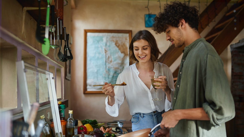 A happy couple cooks together in their kitchen.