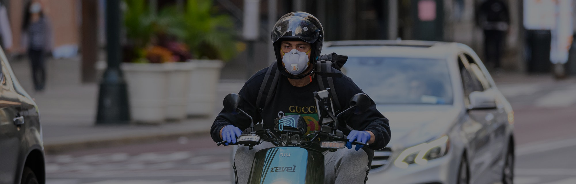 A rider with a helmet and face mask on can be seen riding a Revel scooter. Behind him is a car.