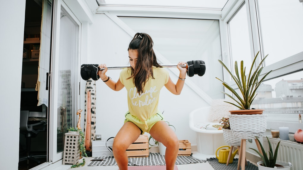 A young woman does weighted squats on the enclosed balcony of her apartment building.