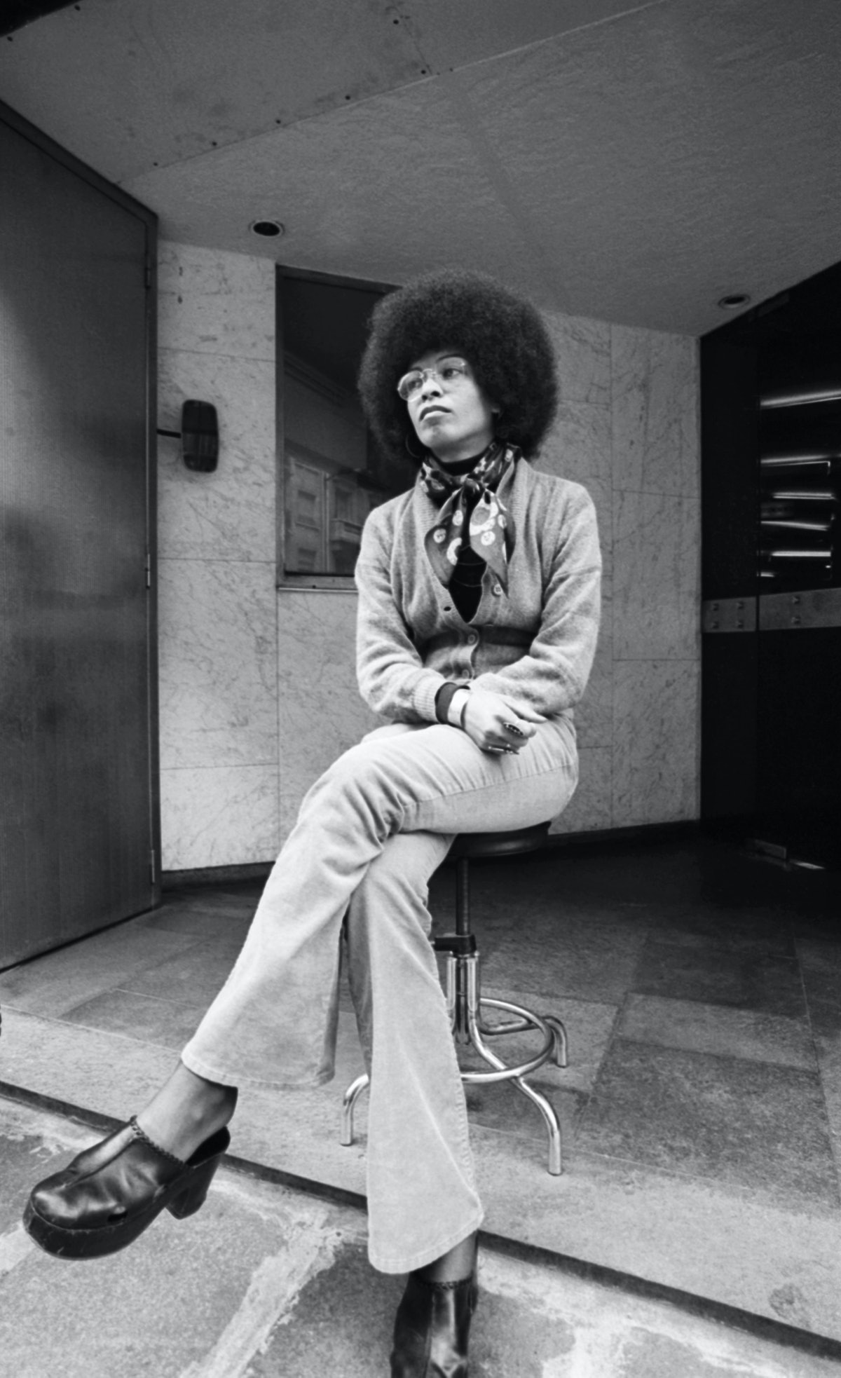 Angela Davis wears cardigan, turtleneck, and clogs in the 1970s.