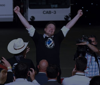 Elon Musk, wearing a SpaceX T-shirt, cheers with both arms up.