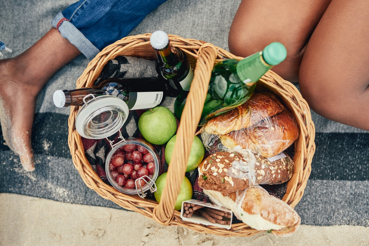 Two women sit next to a picnic basket filled with bread, fruit, and drinks.