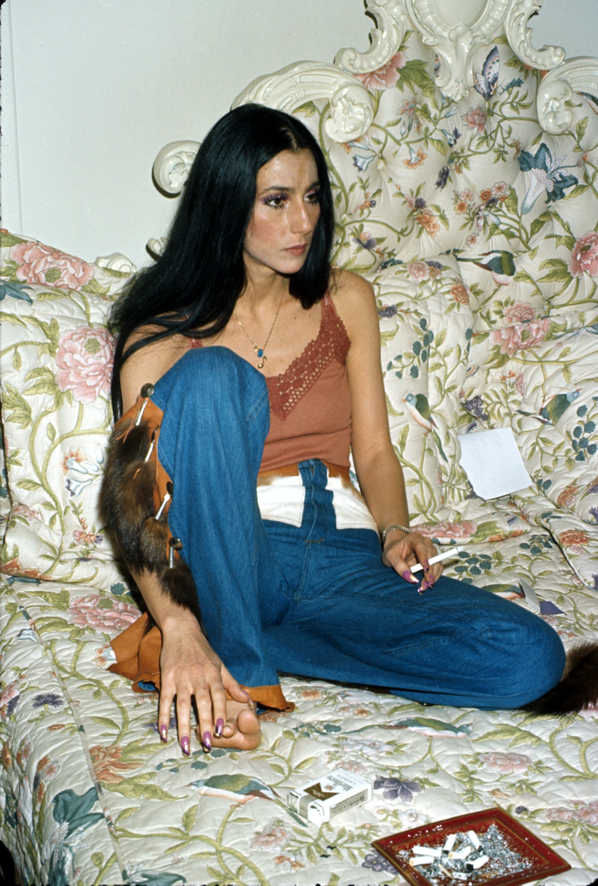 Cher wears wide leg jeans with a spaghetti-strap camisole with lace trip in the 1970s.
