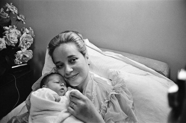 A mom holding her baby and smiling is pure bliss in this vintage maternity ward photo.