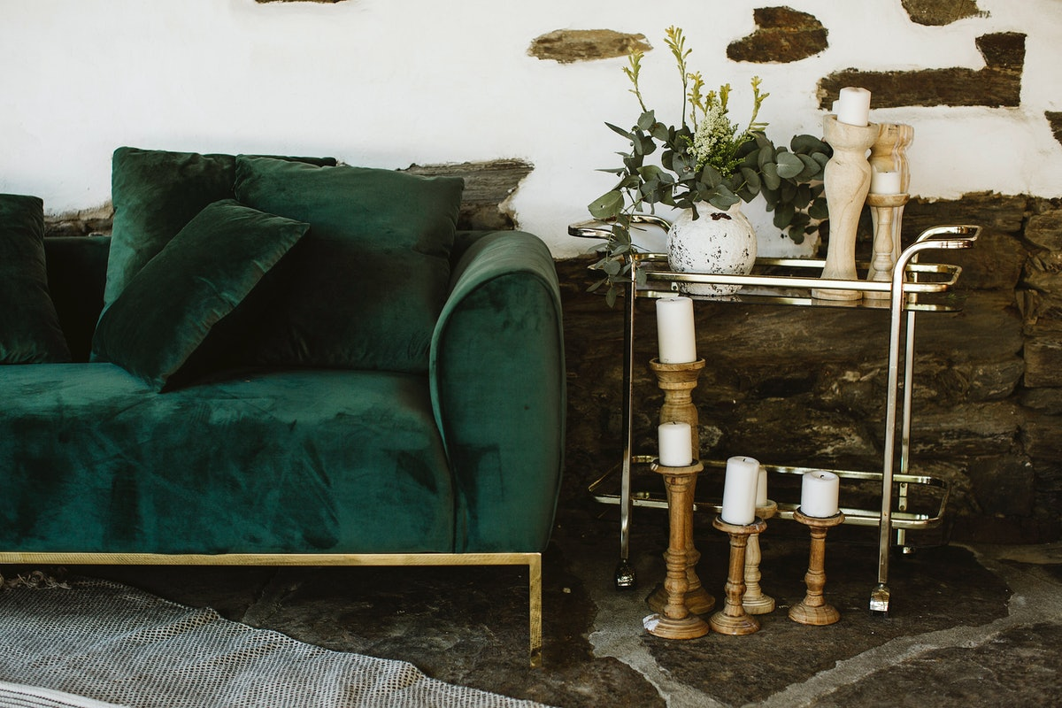 A green velvet couch sits outside against a white brick wall and next to a rack of candlesticks.