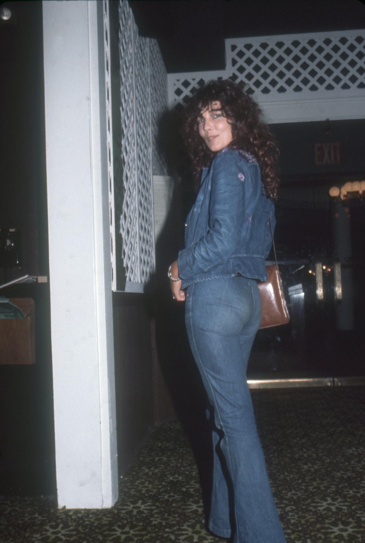 A woman wears canadian tux, denim on denim look in the 1970s.