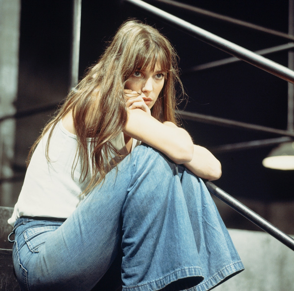 Young woman wears a basic white tank with flared jeans in the 1970s.