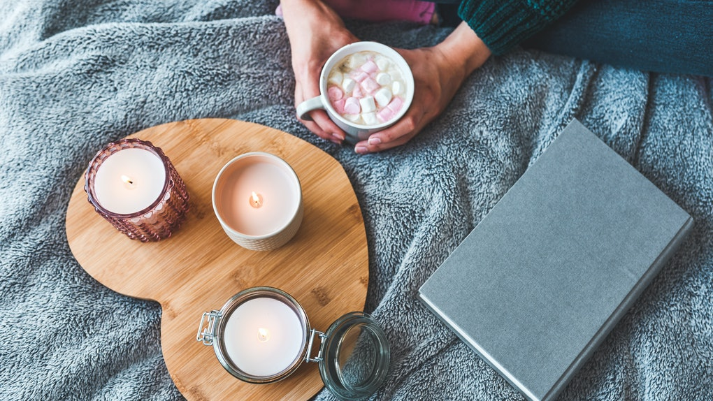 A young woman sits with a mug of hot cocoa, blanket, book, and three candles on heart-shaped wooden board.