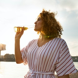 A woman drinks a beer while on the water. This article describes signs your body can't tolerate beer.
