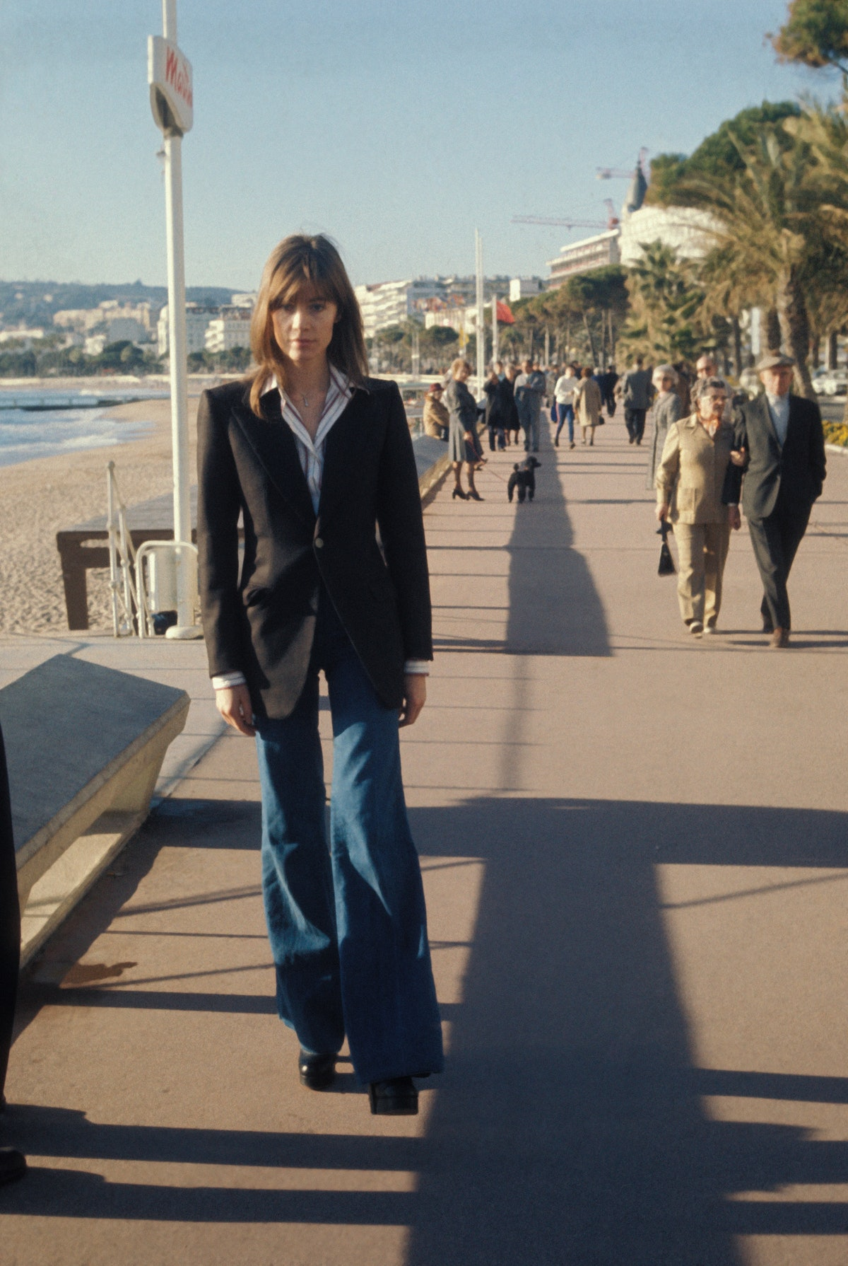 Woman wears a classic black blazer with flared blue jeans on the boardwalk in the 1970s.