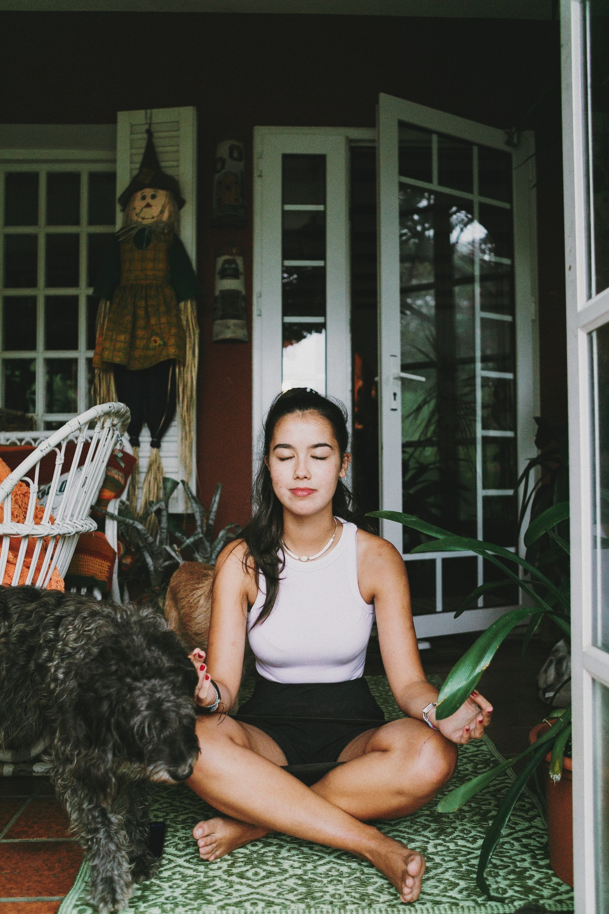 A young Asian woman sits on her porch and meditates on a rug while sitting next to her dog.
