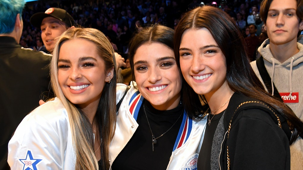 Addison Rae, Dixie D'Amelio, and Charli D'Amelio, attend a basketball game.