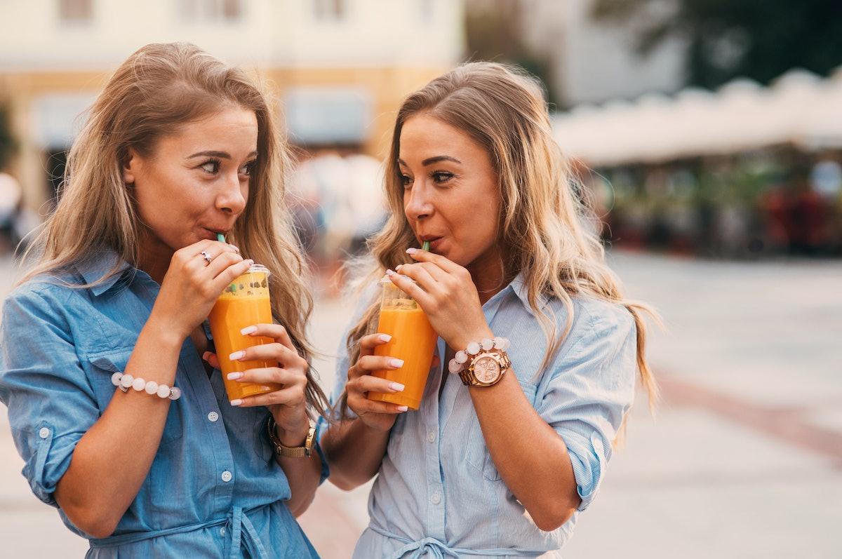 Twins wearing matching rompers, drink orange drinks.