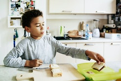 young boy packs sandwich into lunchbox in kitchen