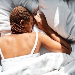 A woman with braids lies facedown in bed. This article details warning signs of hypoglycemia doctors want women to know about.