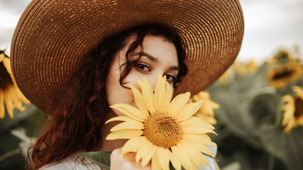 A young woman wearing a large sun hat holds a sunflower up to her mouth while posing for a picture.