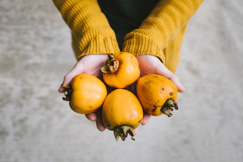 A woman holds persimmons. Vitamin C is marketed as a booster for the immune system, but it doesn't help as much as you think.