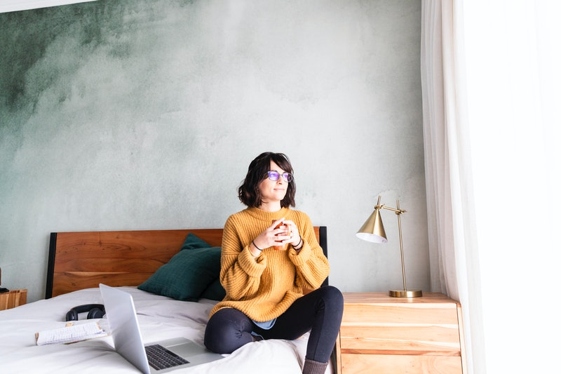 A woman sits in bed with a cup of tea. Does the flu affect your period? OB-GYNs explain how the flu can mess with your menstrual cycle.