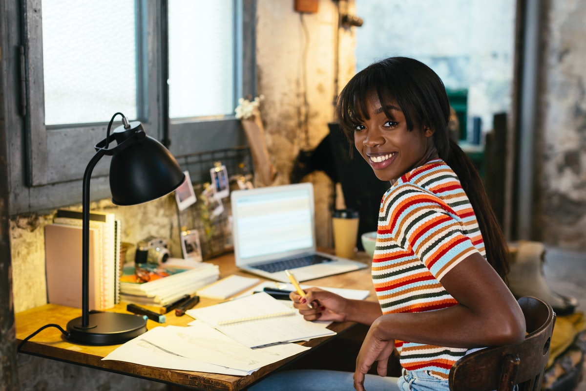 A happy woman sits at her work from home desk.