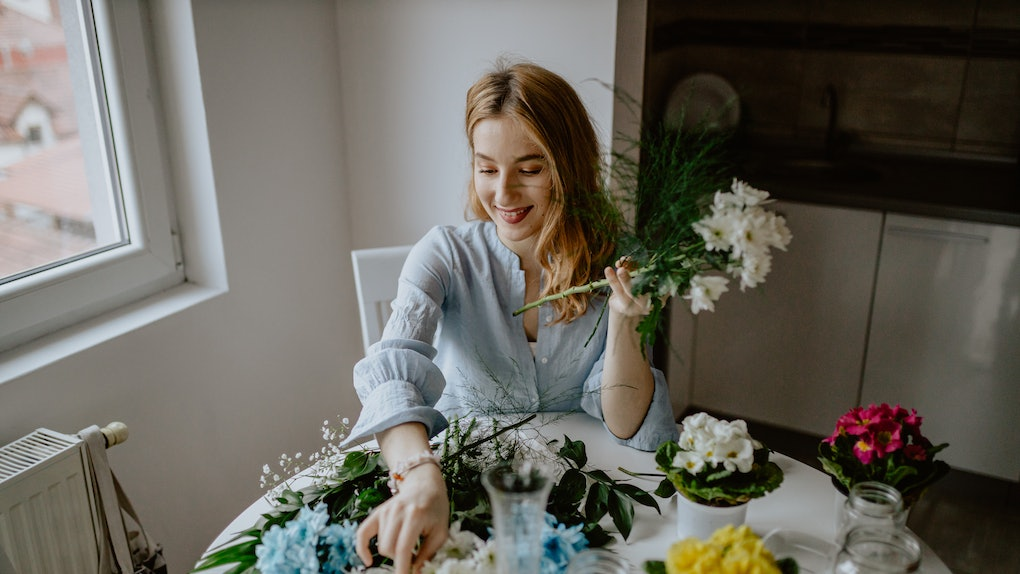 A woman arranging some flowers for a DIY craft at home.