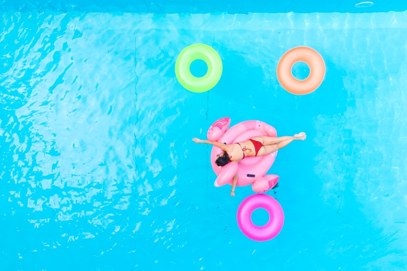 A woman swims on a flamingo pool float. Taking time off in a pandemic has benefits for burnout, experts say - here's how to take time off during coronavirus.