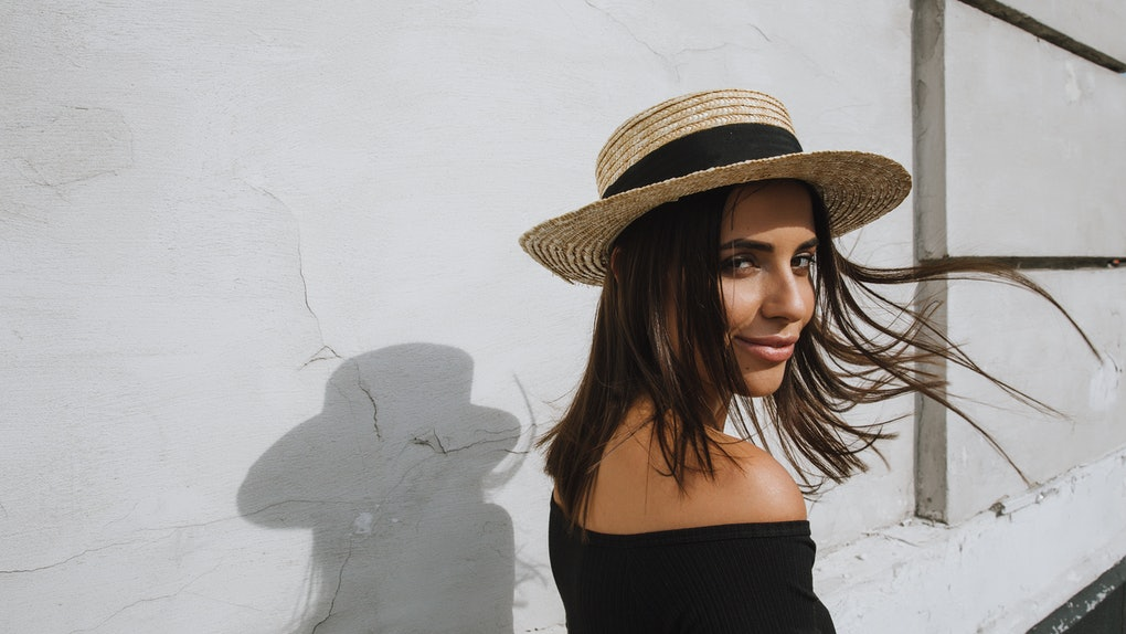 A young woman poses with her shadow in the middle of summer while wearing a hat.