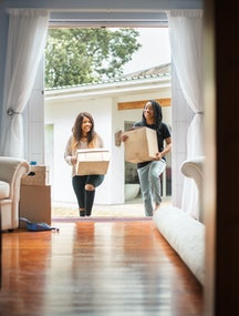 Two people carry boxes into a new house. If you're planning to move during the covid pandemic, doctors explain how to do so safely.
